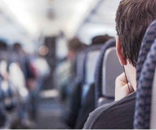 Jeune homme dans l'avion avec écouteurs